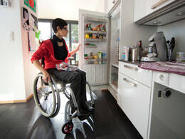 Frau im Rollstuhl in barrierefreier Küche